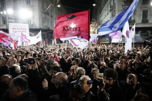 A supporter of radical left Syriza party waves party flag as opposition leader and head of the party Alexis Tsipras delivers speech during a campaign rally in central Athens